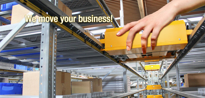 A human hand is moving a shuttle system in a warehouse.